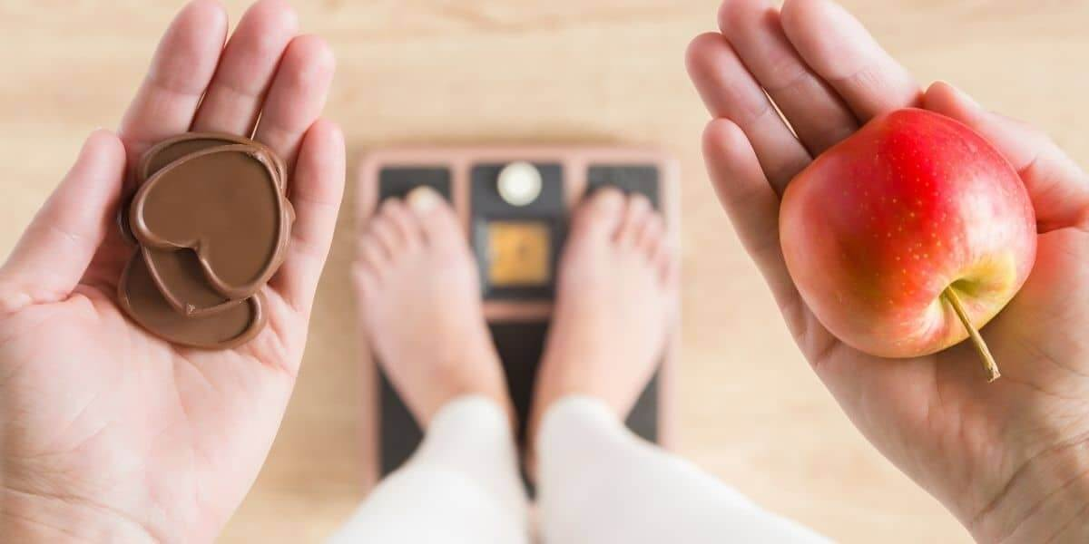 Woman using a scale and trying to decide what supplements to take to lose weight